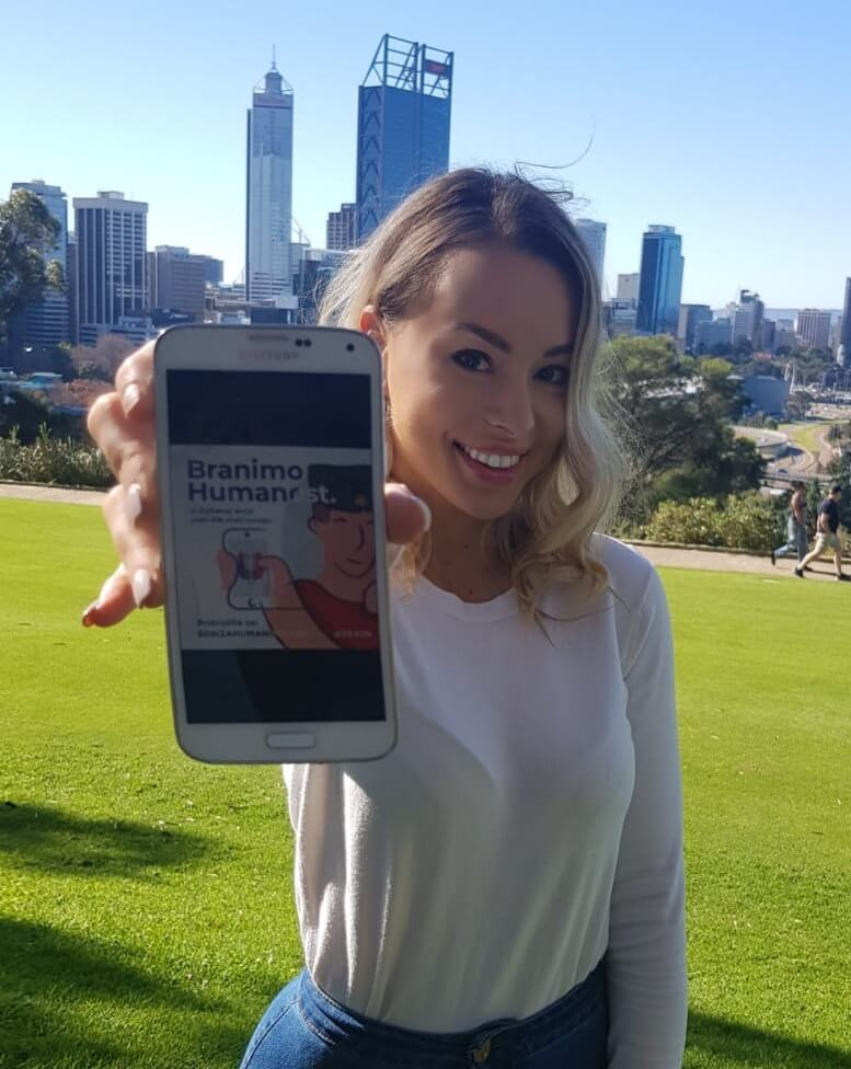 Female 28. Jun member holds phone showing image for humanitarian cause